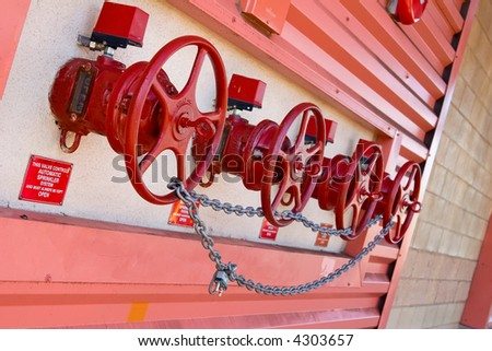 Sprinkler main shut off valves outside a building chained up - stock photo