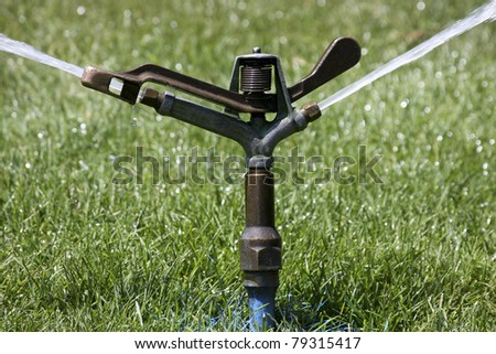 sprinkler system spraying water on a lawn - stock photo
