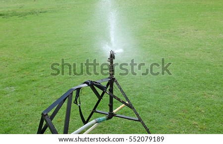 sprinkler watering the grass in the green field.