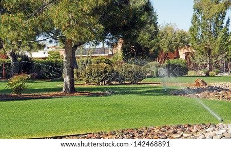 Sprinklers water the grass in park - stock photo