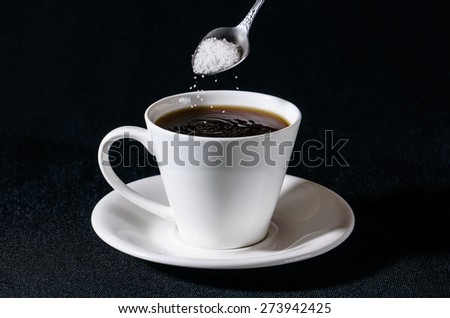Sprinkling of sugar in a white cup of coffee - stock photo
