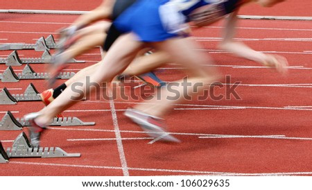 sprint start in track and field in blurred motion - stock photo