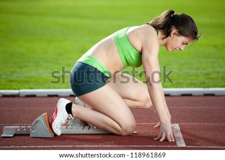 Sprinter in the starting blocks, getting ready to go - stock photo