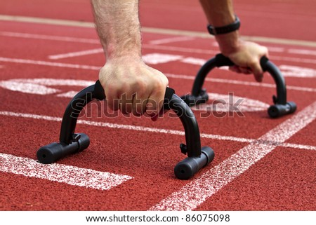 Sprinter on start line makes workout - stock photo