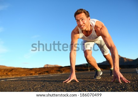 Sprinter starting sprint - man running getting ready to start sprinting run. Fit male runner athlete training outside on road in beautiful mountain landscape nature. - stock photo