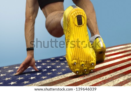 Sprinter with spikes is in start position on grungy US flag - stock photo