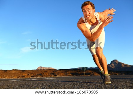 Sprinting man running. Runner sprinter at fast speed training towards goals and success. Fit muscular male athlete in workout outdoors on road. - stock photo
