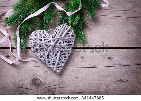 Spruce branches  and rustic  Christmas heart  on  vintage  wooden background. Christmas background. Selective focus. Place for text.