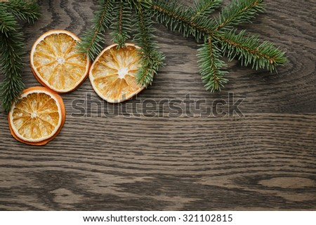spruce twig with dried orange slices on oak table, christmas background - stock photo
