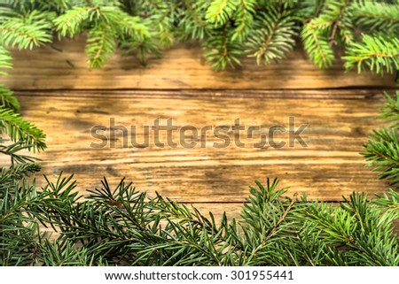 Spruce twigs on a wooden background useful as christmas background in vintage style. Arrangement in frame pattern. Focus on closest twigs. - stock photo
