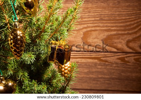 Spruce with golden decoration on the wooden background