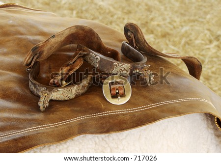 Spurs and chaps resting on hay bales. - stock photo