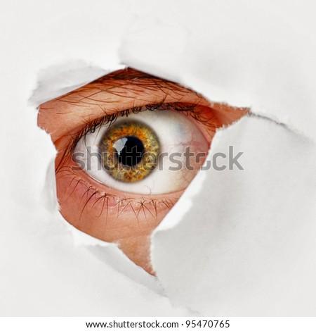 Spy eye peeking through a hole in the paper - stock photo