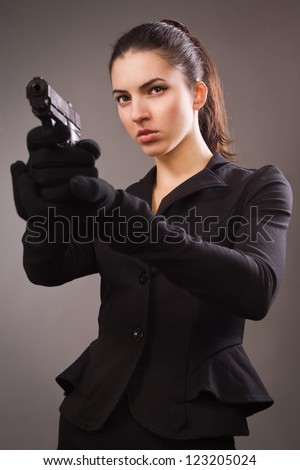 Spy girl in a black suit shoots a gun