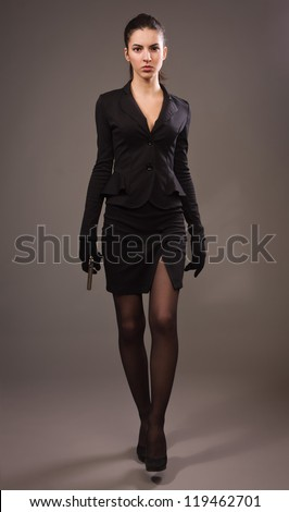 Spy girl in a black suit with gun