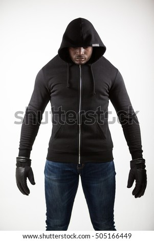 Spy in a hoodie standing against white background