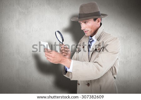 Spy looking through magnifier against white and grey background - stock photo