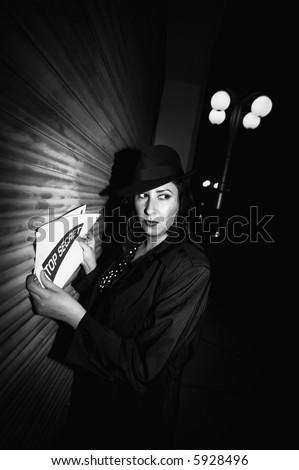 Spy with top secret documents in an industrial alley. - stock photo
