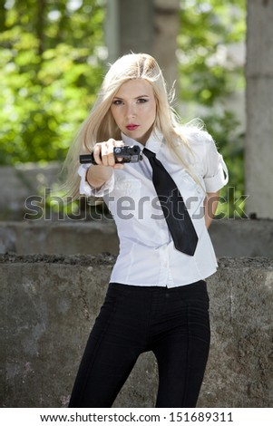 spy woman in white blouse and tie, aiming with a handgun - stock photo
