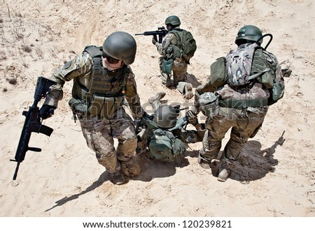 Squad of soldiers evacuate the injured fellow in arms in the desert - stock photo