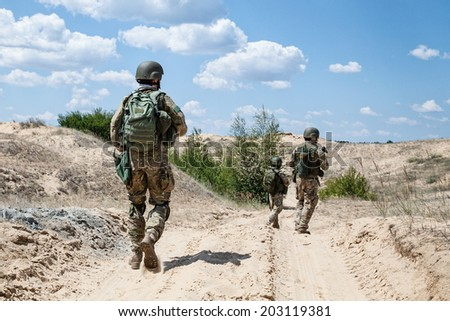 Squad of soldiers patrolling across the desert - stock photo