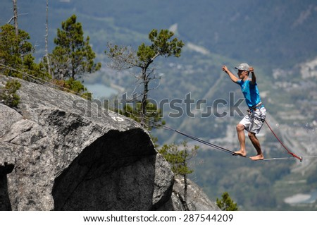 SQUAMISH, BC, CANADA - JUNE 13, 2015: An adventure athlete walks the highline rigged across the gully of the Stawamus Chief in Squamish, BC, Canada, June 13, 2015.  - stock photo
