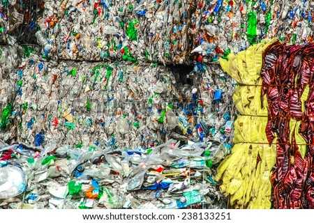 Square bales of wrapped plastic bottles ready for the melting process. - stock photo