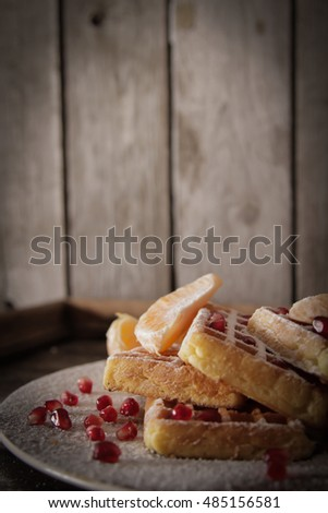 Square Belgian waffles with a tangerine and pomegranate and sprinkle with powdered sugar