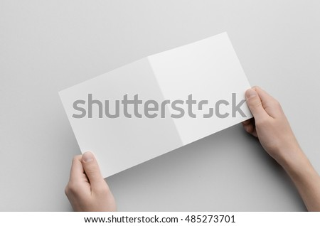 Square Bi-Fold Brochure Mock-Up - Male hands holding a blank bi-fold on a gray background.