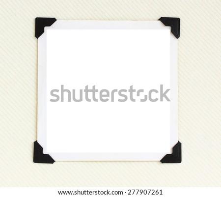 Square blank photo with black corners on retro photo album - stock photo
