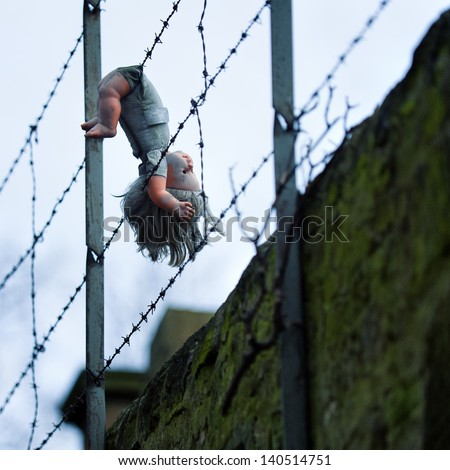 square color image of doll hanging from barbed wire fence