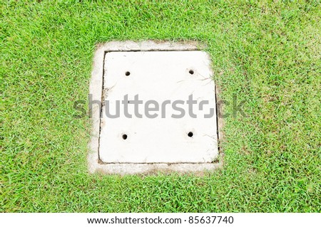 Square drain covers on the grass of city park. - stock photo