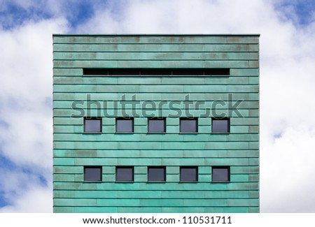 square facade with copper strips against cloudy sky - stock photo