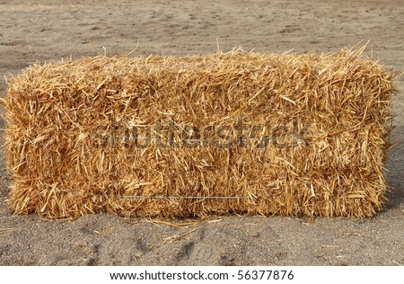 Square hay bale on a sand background - stock photo