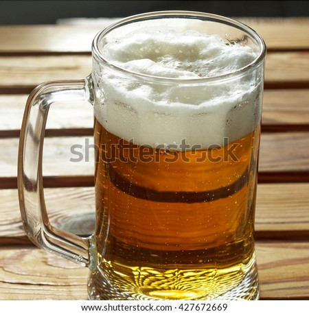 Square image. A mug of beer with froth closeup. Glass of beer on a wooden table - stock photo