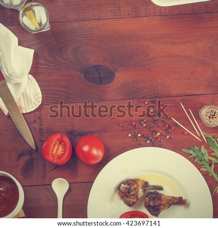 square image. Vodka, gin, tequila in a glass with ice, fried chicken legs and fried chicken wings , Cherry tomatoes, Spices, Italian food . top view, closeup - stock photo