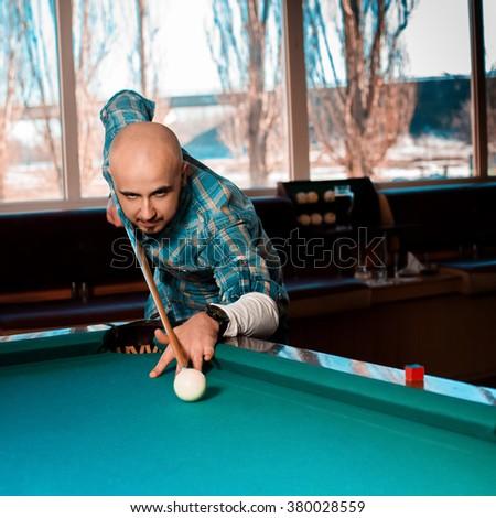 Square Photo Man preparing to hit the cue ball on a pool billiards. Billiard game concept. American pool billiard. Pool billiard game. - stock photo