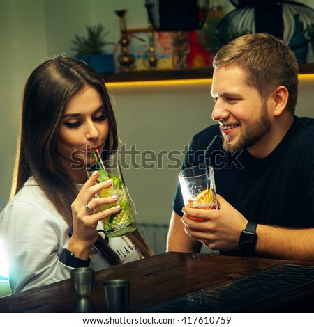 square photo of attractive couple flirting and drinks cocktails at the bar. nightlife concept