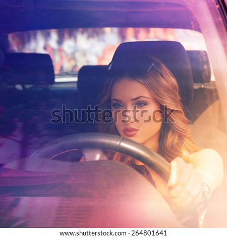 square photo of young concentrated sexy girl model driving car - stock photo