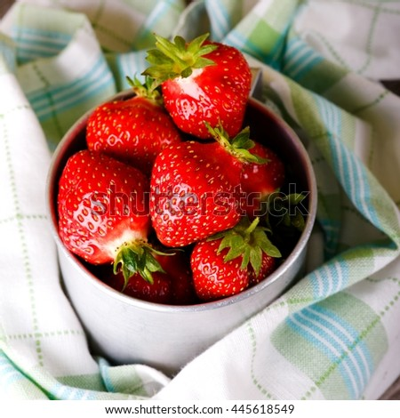 Square photo with aluminum cup full of red strawberries. Harvested ripe strawberries in old cup with towel around. Checkered towel with juicy berries. Fruit in metal vintage cup. - stock photo