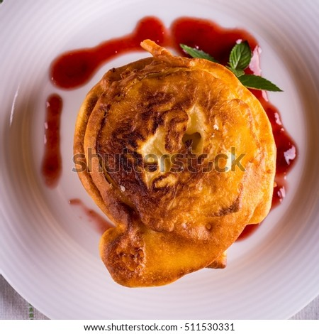 Square photo with top view on few cinnamon apples coated in pancake dough. Sweet food placed on white plate and cloth with spilled red fruit jam. Piece of green mint herb next to tower.