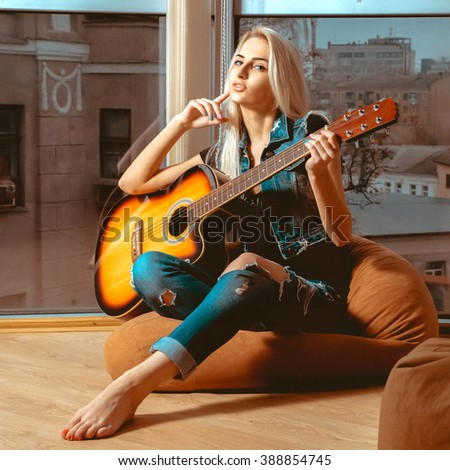square picture modern young girl with a guitar in hands. Girl with guitar. Woman playing guitar. leisure with guitar. - stock photo