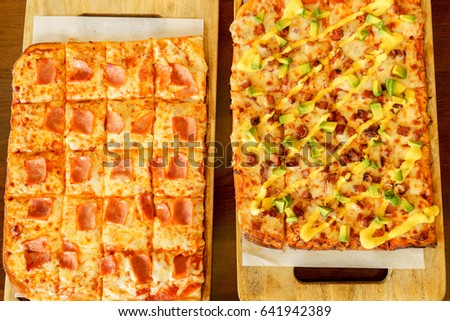 Square pizza with organic ingredients on a wooden board on a restaurant background.