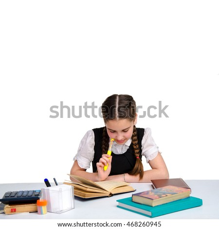 square portrait of young schoolgirl in uniform doing her homework isolated on white background