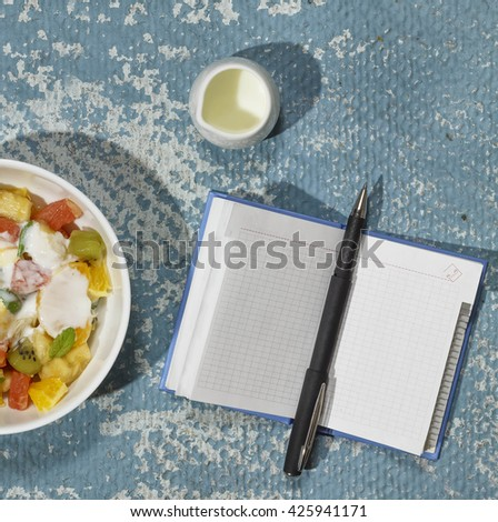 Square shot.  bowl with fruit salad , notebook. Proper nutrition, diet - stock photo
