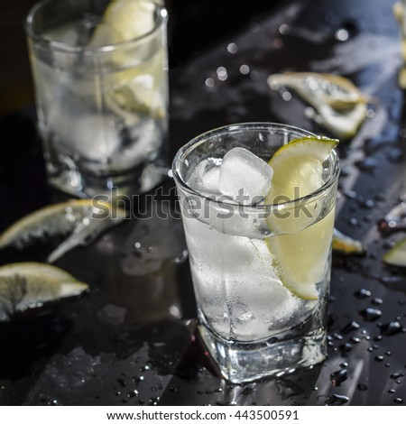 Square shot. Closeup of vodka with ice and lemon and lime on a black background. Reflection. Passion. Elegance