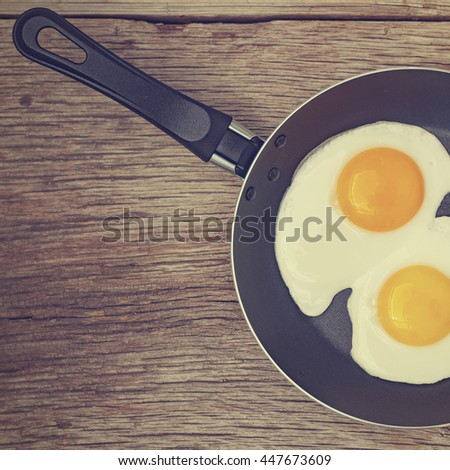 Square shot. Fried egg in a frying pan on a wooden background. - stock photo