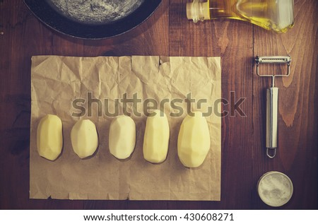 Square shot. Potatoes, set for fries, old frying pan, olive oil, knife to clean the vegetables on a brown wooden table, country style, top view, closeup - stock photo