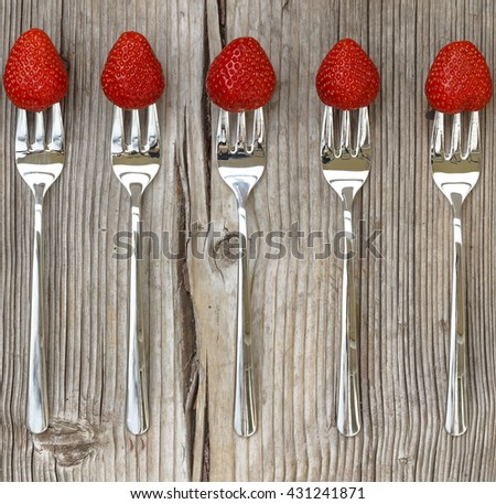 Square shot. Ripe strawberry on a fork on a worn wooden background. - stock photo