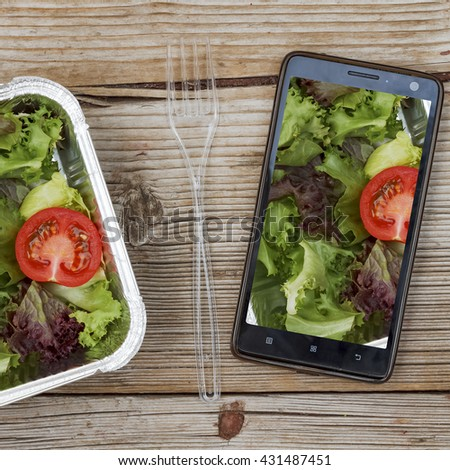 Square shot. Smartphone and wholesome food in disposable containers on a wooden background, shopping online. Concept: Proper nutrition, catering, business lunch.  - stock photo